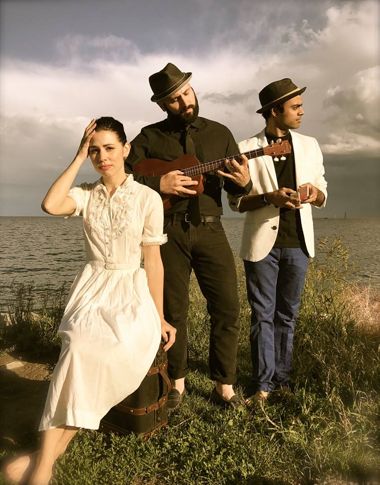 Julia Porter, Chai Lavie, Shawn DeSouza-Coelho pose in a field.