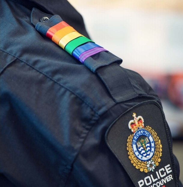 Vancouver police badge with rainbow strips above on shoulder.