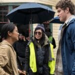 A photo of The Half of It director Alice Wu on set with actors Leah Lewis and Daniel Diemer.