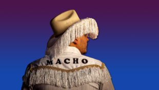 "Texas-based artist Jose Villalobos, in a fringe-lined cowboy hat and a jacket reading ""macho."""