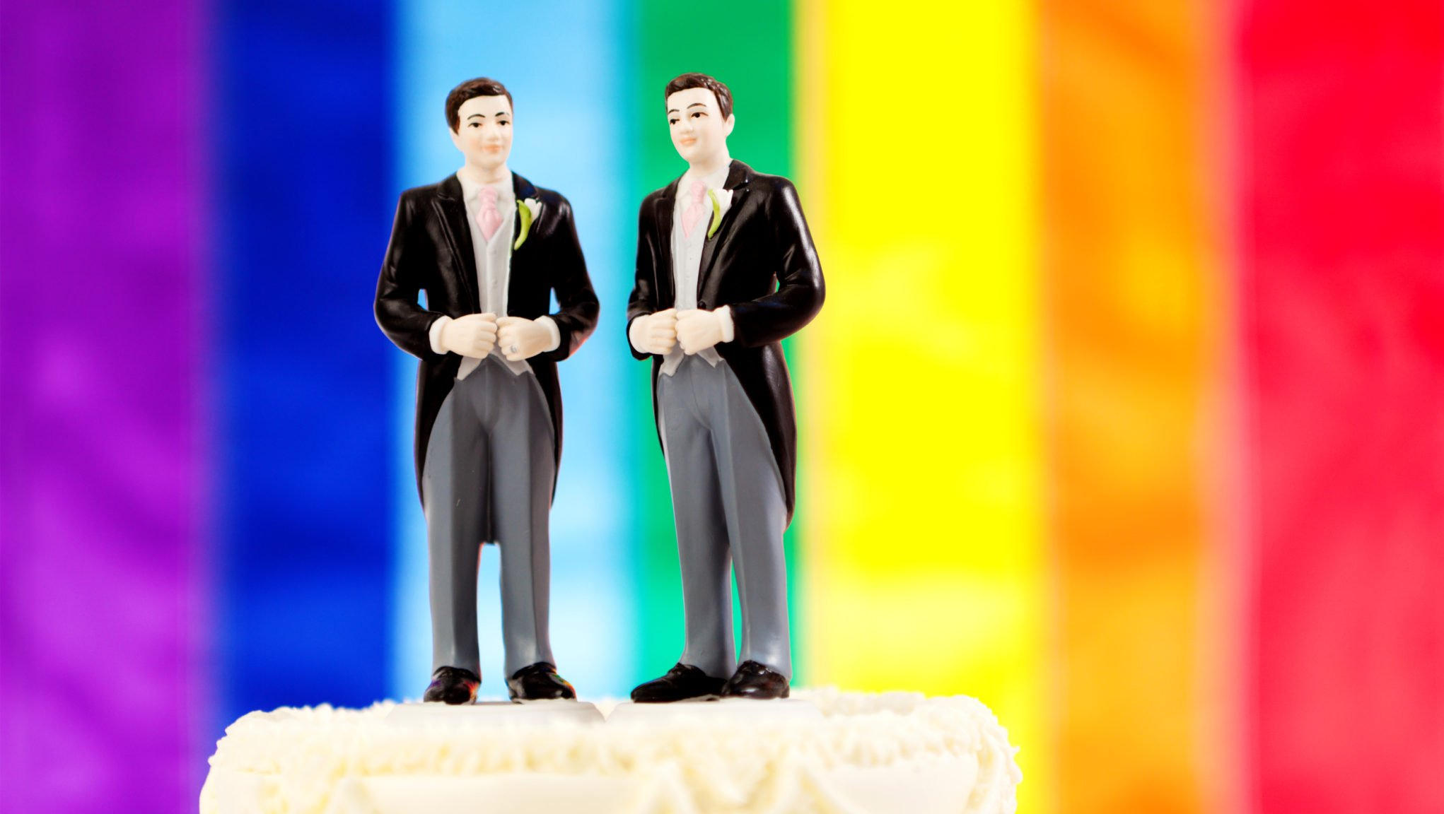 A wedding cake topper of two men in suits on a rainbow background, signifying marriage equality