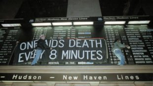 Members of the AIDS activism group ACT UP hang a banner across the train schedule board in New York's Grand Central Terminal, in 1991. Hundreds of protesters marched through the station during rush hour. Some are comparing the AIDS crisis to the current COVID-19 pandemic.