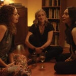 Still from Wendy Jo Carlton's 'Good Kisser.' Three woman sit in a circle on the floor with a bottle of wine between them.